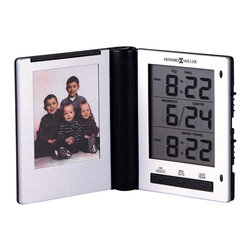 """Howard Miller - Folding Digital Travel Alarm Clock with Photo - Bring your loved ones along with you on your long trips, and make sure you get home on time��_this handy clock holds a photo to remind your of your life at home, while three displays count off the time of day, the date, and a world-clock time. The piece is slim and attractive, finished in silver and black. * A slim folding travel alarm clock with a photo holder. Black and brushed silver finish. . The LCD displays the month, day, and time in a 12- or 24-hour format. . Dual time format, snooze alarm, and display light. . Quartz, alarm movement includes battery. . H. 3"""" (8 cm). W. 2-3/4"""" (7 cm) . D. 3/4"""" (2 cm) closed"""