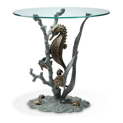 SPI - Bronze Finish Seahorse Glass Top End Table - This unique sea life glass top end table features a sculptured aluminum Seahorse situated within a coral branch formation and kelp leaves. A clear round plate glass top is supported by the coral and kelp branches that are mounted on an aluminum base resembling the ocean floor. Several tropical fish swim near the bottom with a few sea shells lying on the base. The table measures 22 inches tall, 22 inches in diameter. It makes a great gift.