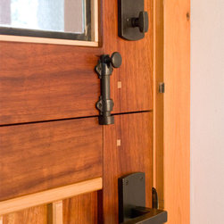 Dutch Doors - Hardware detail on custom dutch doors. Typically a deadbolt is required for the top panel, a dutch cane bolt to secure the panels together, and a passage knob for the bottom panel. These doors are made from Padauk solid wood and feature beautiful leaded glass.