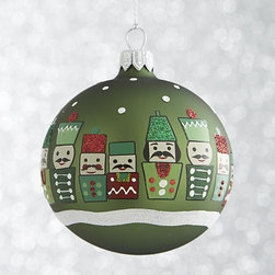 "Green Nutcracker Ball Ornament - Entire ""armies"" of stylized modern nutcracker soldiers are handpainted with detailed mustaches, hats and uniforms with glitter accents. They stand in snow on handmade glass ornaments with matte green, red or white finishes."