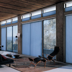 Sliding Glass Doors - This space is unique with the mixture of texture and finishes.  The overall feel is masculine but don't be fooled by this modern cabin because the space is still warm and inviting. The ceiling is a great example of using reclaimed wood and pairing it with the concrete flooring is visually stimulating.  The wall of transom windows and sliders would normally be a energy nightmare but with the cellular technology from Hunter Douglas, the exterior weather elements are no longer a problem.  Duette Architella Shades can reduce energy loss up to 50%!  In addition, replacing old verticals with this product, which can be pulled across without the use of cord loops or pull cords, significantly reduces a child hazard.