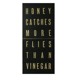 """Sugarboo Designs - Honey Catches More Flies Vintage Sign - Handmade vintage sign with the message """"Honey Catches More Flies Than Vinegar"""". This 44"""" x 20"""" vintage wood sign adds a touch of love and care to a bedroom, kitchen, or office. This decor piece offers a thoughtful message to share with your own family. It is also a loving housewarming present for a dear friend, son or daughter, or other family member to bring well wishes to their home. The sign is available in Black. It is easy to hang as wall art. The sign also creates a captured moment when placed on a desk or counter for a more casual feel. The artist mixes rustic materials with an updated, clean style to create a piece of decor art that adds charming character to your home.  Each sign is made upon customer order in the artist's Georgia-based studio using a specialized technique that paints directly onto the wood rather than using canvas.   About the Artist: Rebecca Puig is the artist behind Sugarboo Designs. Sugarboo is a family business that Rebecca and her husband, Rick, started in 2005. The name """"Sugarboo"""" came from a couple of nicknames she has for her children, Jake and Sophie. They are the main inspiration for Sugarboo because Rebecca always wants to create products that remind us of the ones we love. As a little girl, Rebecca loved to paint and create things. She attended the University of Georgia graduating with a Studio Art degree. Rebecca is inspired by her family, nature, animals, old things, childrens' art and folk art. She also loves juxtaposing old and new, light and dark, serious subject matter with fluff and anything with a message. Rebecca believes in putting good out into the world whenever possible. Her hope is that each Sugarboo piece she creates will add a little good into the world.   Product Details:"""