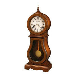 Howard Miller - Cleo Mantel Clock in Chestnut Finish - Finished in Chestnut on select Hardwoods and Veneers, this traditional wooden mantel clock features a turned finial and seeded Glass in the lower door. Aged dial with worn Black roman numerals, wood bezel, Black hour and minute hands and convex Glass. The dial is specially inscribed with an 84th Anniversary Edition inscription (through 2010). Antique Brass-finished pendulum bob suspended on a wood stick pendulum. Quartz, triple-chime Harmonic movement plays Westminster, Ave Maria, or Bim-Bam chimes, with volume control and automatic nighttime chime shut-off option. Requires 2 C size batteries (not included). 9 1/4 in. W x 4 3/4 in. D x 24 1/4 in. H