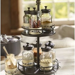 """Rotary Spice Rack with 9 Glass Jars, Bronze finish - Two rotating round tiers, each holding multiple spacious spice jars, make this kitchen storage piece exceptionally attractive. Each jar is made of thick glass with a lid that seals for freshness. Rack: 8.5"""" diameter, 15"""" high Jar: 2.5"""" diameter, 5"""" high; 6.5 fluid-ounce capacity Made of iron with a bronze finish. Includes nine blown-glass spice jars with iron lids. Replacement Spice Jars are available and can be monogrammed with up to 9 characters. Monogramming is available at an additional charge. Catalog / Internet only."""