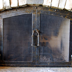 The hammered Fireplace Screen - These two fireplace screens are hand hammered and form fitted to the stone openings. Hand made latches lock tightly but open easily with handles that do not get hot. Also available with glass doors.