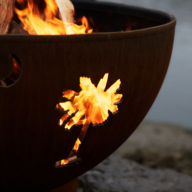 """Fire Pits - Great for Fall and Winter - With the Tropical Moon 36"""" Fire Pit, you'll almost be able to feel the rush of saltwater over your skin and imagine the reflection of the crescent moon in the placid water. Its precision cut moon and palm tree design will fit perfectly anywhere from coastal and tropical settings to climates that need a little bit of extra sunshine. This wood burning fire pit is made from the heaviest gauge steel available, ensuring that you'll have this functional piece of fire pit art as part of your outdoor collection for many years in the future. The Tropical Moon 36"""" Fire Pit is not just a practical fire pit; it is a piece of art in its own right. It has a standard iron oxide patina finish on the outside. The iron oxide patina will darken a little with time before becoming permanent. The inside is coated with a high temperature resistant paint and has a rain drain in the bottom. The base of the fire pit has an inside weld to give a smooth and clean look on the outside while maintaining the integrity of the piece."""