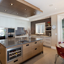 West Van 3 - This kitchen has a combination of Rift cut White Oak on the Island and ceiling with a bronzed metal leg system and painted off white cabinets around the perimeter.