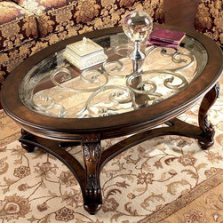 Signature Design by Ashley - Oval Glass Top Cocktail Table - Every flourish brings added beauty to the Norcastle cocktail table. Elegant filigree swirls float just beneath a glass inlay on the oval surface. Wood framing offers a burled finish that adds highlights to cabriole legs featuring acanthus carvings and a shaped base. Color/Finish: Dark Brown. Dark Brown finish on select birch veneers and hardwood solids. Cast filigree under clear beveled float glass. Shapely legs and stretchers. Some assembly required. 48 in. W x 34 in. D x 20 in. H