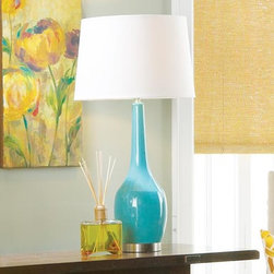 Nanette Lamp - Fresh color perks up your space and this blue lamp is just the ticket. The glossy base has a graceful tapered neck and a metal base with an antique silver finish. Hardback drum shade is in white linen fabric. UL approved.