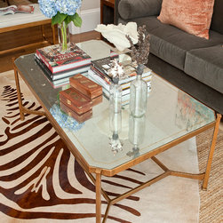 London Coffee Table - A hand-gilded, wrought-iron openwork base gives our London Coffee Table handsome looks, while its eglomise glass rectangular top brings it a sense of delicacy — a perfect balance for a formal yet contemporary interior. With slender legs, this sophisticated design is visually light, making it an ideal for small or crowded spaces!