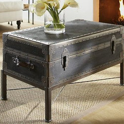 "Ludlow Trunk with Stand Coffee Table, Black - Artfully finished to replicate the look of weathered canvas and detailed with brass nailheads that secure the edge braces and corner guards, this piece resembles vintage trunks that have been repurposed to serve as occasional tables. Wood-lined compartments allow stow space for blankets, games and more. 36.5"" wide x 20.5"" deep x 20"" high Crafted of wood that's textured to resemble weathered canvas; finish is hand-applied in antique black. Detailed with reinforced metal corners finished in antique bronze. Trunk is fixed to an antique bronze metal base. Decorative buckles. Features safety hinges to prevent accidental closure. Detailed with 2 handles and rivets. View our {{link path='pages/popups/fb-media.html' class='popup' width='480' height='300'}}Furniture Brochure{{/link}}."