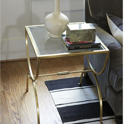 Ballard Designs - London End Table - Antique brass finish. Clear glass top. Light and elegant, our London End Table is designed with a sophisticated hourglass frame that goes from traditional to modern with timeless style. Crafted of heavy stainless steel with bar stretcher and tiered button detail. London End Table features: . .