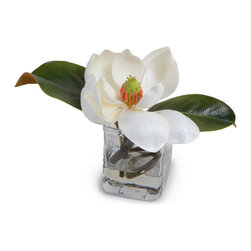 """New Growth Designs - Magnolia Flower - Beautiful in its simplicity and purity, this single reproduction cream Magnolia blossom with Magnolia leaves is arranged by hand in a small glass cube vase, 9"""" long x 5"""" wide x 7"""" high."""