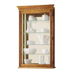 """Howard Miller - Montreal Wall Curio Cabinet - This versatile wall cabinet was made using superb woodworking skills. It has acanthus leaf molding on the pediment and reeded columns at the sides. The glass-mirrored back beautifully reflects each collectible. Four adjustable glass shelves offer many levels of adjustment. Access your collectibles through a hinged, front door Features: -Golden oak finish.-Hardwoods and veneers construction. -Mount on the wall or set on a mantel or bookcase with a specially designed """"no-tip"""" base."""