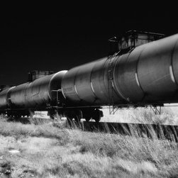 """Train Cars, Del Norte - Large-Scale, Limited Edition Photography - Line and perspective are the key elements within this dramatic, 48"""" x 20"""" fine art photograph by Cody Brothers. The line of train cars, the tankers and the fence line disappearing into the house are what catches the eye and there is beautiful texture provided by the grass in the foreground and depth created by the clouds in the distance."""