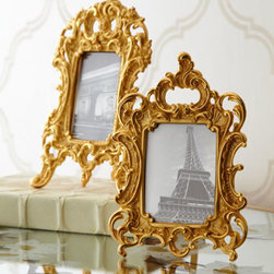 """BANCHI - BANCHI Medium Baroque Frame - Ornate tabletop picture frames in high Baroque style feature wonderfully asymmetrical scroll and leaf designs. Handcrafted of 24-karat gold-plated brass. Small frame, 4.25""""W x 0.75""""D x 6.25""""T. Medium frame, 5""""W x 0.75""""T x 7.5""""T. Made in Italy."""