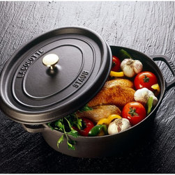 Staub - Staub Oval Cocotte - 7 qt. - Black Matte - 1103325 - Shop for French Ovens from Hayneedle.com! Incredible heat retention and a self-basting lid differentiate the Staub Oval Cocotte - 7 qt. - Black Matte. Every dish will retain the full flavor of each ingredient thanks to the dozens of well-placed spikes on the underside of the lid that continuously baste the food below and the extra-heavy lid that seals in moisture. After enjoying your delicious meal pop the pan into the dishwasher. The high-quality enamel coating resists scratches and will never discolor.About Staub CookwareFrom professional chefs to home cooks people with a passion for cooking rely on Staub cookware. Combining the utility of cast iron with the latest technology available Francis Staub designed his first enameled pot in 1974 in the Alsace region of France. Known for performance style and durability Staub has become the benchmark for enameled cast-iron cookware. Ideal for braising searing roasting and caramelizing food Staub's signature pots - called cocottes - feature an enameled interior with a matte black finish. Resistant to rust chipping and cracking cocottes are available in round and oval shapes in a variety of sizes and colors. Just right for slow-cooking food Staub cocottes are designed to provide even heat distribution excellent heat retention and continuous self-basting. The inside of each heavy snug-fitting lid features a series of bumps (or self-basting spikes) to allow continuous natural basting by distributing moisture throughout for extra flavor and tenderness. In addition to its signature cookware which is perfect for serving at the table Staub also offers pans for frying sauteing grilling and roasting as well as a variety of teapots accessories and gourmet specialty items.