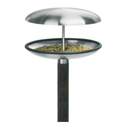 Blomus - FUERA Bird Feeder by Blomus - The Blomus FUERA Bird Feeder will attract many song birds to your backyard garden and transform a little patch of grass into an extraordinary oasis.  While the stainless steel top protects food from rain and snow, this birdfeeder has the dual function of becoming a bird bath too. Just remove the stainless steel top and voila! The FUERA Bird Feeder is made from stainless steel and wood.   Blomus, headquartered in Germany, specializes in the design and manufacture of modern home and office accessories. The Blomus line includes modern desk, kitchen, table top, office, bath, garden, and home accessories.The Blomus FUERA Bird Feeder is available with the following:Details: Stainless steel body Wooden base Dual function birdbath or feeder Designed by Susanne AugensteinShipping: This item usually ships within 2-3 business days.