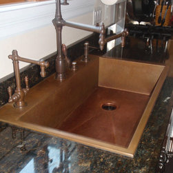 A copper sink that replaced a stainless sink. Retrofit Copper Sink - Copper sinks replace stainless sinks because they are easier to maintain and add warmth to the kitchen. Copper sinks blend well with stainless appliances. Single bowl copper sinks seem to be, by far, the most popular replacement for old fashioned double bowl sinks. Our copper sinks can be top or under mounted. Our top mount copper sinks feature an architectural edge, giving a very custom look. Since all of our copper sinks are custom made, we can size them to fit just about any opening.  The faucet suite shown is the Towson, by Waterstone. Available at http://www.theUSAhome.com