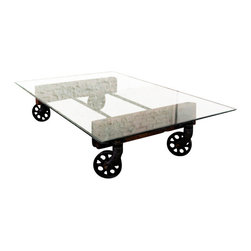 Nuevo Living - V35 Coffee Table - Your eclectic style is really on a roll with this unique piece. The tempered glass top sits on a hardwood base with reclaimed cast iron wheels, transforming a coffee table into a true conversation piece.