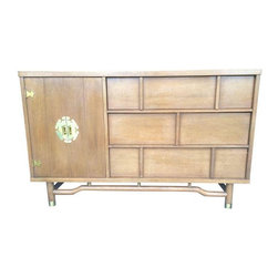 """Pre-owned Mid-Century Chinoiserie Sideboard - Gorgeous and unique honey colored, asian influenced mid century sideboard! This piece is so versatile! Perfect for dining room sideboard, tv credenza, dresser, front hall table, etc. It has one door that opens and three drawers. Drawers all work smoothly. Has great lines stunning brass accents like the 6inch brass face plate for the door handle! In great vintage condition with just some minor wear marks. The most noticeable are a scratch on the right lower side about .75"""" in size and a patch on the front left corner. Both of these are much more noticeable in the photos because they are in natural lighting. Take note of the second photo of the front corner blemish under indoor lighting, as it isn't as noticeable at all. There doesn't seem to be any brand labels for the piece, but I couldn't find a duplicate online, so it is definitely unique!"""