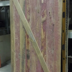 Custom Doors - This is a custom interior sliding barn door. It's made from reclaimed barn wood and still has some red paint still showing. Hand waxed. This door will close off an exercise
