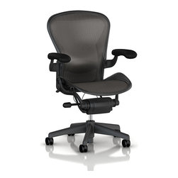 """Herman Miller - Aeron Chair - Patented Pellicle fabric conforms to the user's body and retains its original shape when unoccupied. The Aeron Chair is composed of 64 percent recyclable materials, including aluminum, steel, plastic, foam, and textile. This particular model is a size a chair with graphite frame, classic lead pellicle upholstery, fully adjustable leather arms and adjustable lumbar support. Most of the material used in building each chair is recycled, and most can be recycled again. Height ranges from 36"""" - 40"""""""