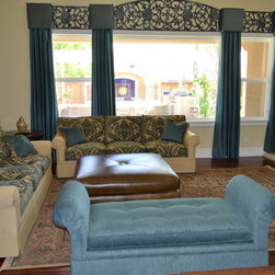 Complete Room Makeover - Custom built and upholstered furniture finish off this beautiful room. Faux Iron insets between the cornice boxes and side panels are the perfect touch. The custom built leather ottoman serves as both a table and a footrest.