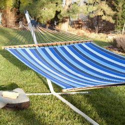 Twin Oaks Cobalt Quilted Sunbrella Fabric Hammock - What's the recipe for the perfect hammock? Well, the Twin Oaks Cobalt Quilted Sunbrella Fabritc Hammock has all the right ingredients – great design, expert craftsmanship, and the finest materials. The comfy hammock starts with two layers of premium Sunbrella fabric quilted over a cushiony 10 oz. polyester fiberfill interior. Sunbrella is the leader in outdoor fabrics: weather, mildew and fade resistant, strong enough for industrial use yet unbeatably soft. The solid white oak spreader bars are finished with all-natural linseed oil, the matching-color rope harnesses of super-sturdy polyester are all hand-tied. With a breezy striped pattern on a reversible bed that's big enough to share. Hanging hardware included. Handcrafted in the U.S.A.About Twin Oaks HammocksThe folks at Twin Oaks believe that quality starts from the beginning - in every fiber of every rope and in every cut of every log. They should know; they've been hand-crafting fine hammocks in their rural Virginia facility since 1967.Their spreader bars begin as locally-harvested white oak logs, which they mill and kiln-dry on site so they're well-seasoned for outdoor use. The completed spreaders are hand-brushed with natural linseed oil and air-dried to maintain the natural beauty of the wood grain. Their macramé harnesses are crafted by hand, then carefully measured and trimmed so that every hammock made is stable and comfortable.Rope hammocks start with yarn specially chosen for weather-resistance and colorfastness, and twisted it into durable rope in all colors of the rainbow. For their fabric hammocks, Twin Oaks chooses only the finest outdoor fabric in the industry and uses reinforced stitching to ensure a sturdy product that will last from season to season. They stand by the quality of their products and back that up with a full two-year warranty – the best in the business.About Sunbrella Sunbrella has been the leader in performance fabrics for over 45 years, offering impeccable quality, sophisticated styling and best-in-class warranties. Sunbrella fabrics are both breathable and water-repellant and, if allowed to dry, will not support the growth of mildew, as will natural fibers. Beautiful and durable, Sunbrella is the name to trust in outdoor furniture.Cleaning and Caring for SunbrellaRegular maintenance is the best way to keep your Sunbrella fabric looking good for years to come. Brush off dirt before it becomes embedded in the fabric and wipe up spills as soon as they occur. For light cleaning, use a solution of mild soap and lukewarm water with a sponge, letting the cleaning solution to soak into the fabric. Rinse thoroughly to remove residue and allow fabric to thoroughly air dry.