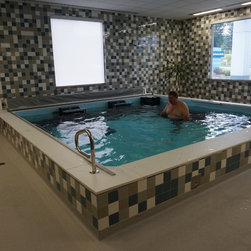 Dual Propulsion Endless Pool® - The bold tile work makes a delightfully edgy environment for this Dual Propulsion Endless Pool (and smartly plays off of the boxy windows). With two swim-current generators, he could swim side-by-side with a friend or family member.