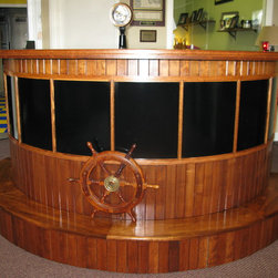 Custom made Boat Bar - If you would like something different for the nautical man cave, this is it. A unique custom made pilot house BOAT bar. This unique Nautical boat bar is made of solid oak pieces and veneers, breaks down into 4 pieces so it can be easily moved. Working port, starboard and searchlight salvaged from a real boat, also includes a ships wheel for that added nautical feel. All lighting on the bar are low voltage high quality L.E.D. and will last up to 50,000 hours, complete with a dimmer dial. Lighting is placed under bar top both front and back of bar. Back of bar also has an outlet for accessories such as a blender can be used. This Custom Pilot House Bar measures about 8 feet wide by about 4 feet deep, 42'' tall. Lots of storage under bar top with some shelving. Designed and built by Shawn Leach