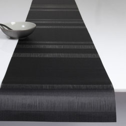 Chilewich - Tuxedo Stripe Table Runner by Chilewich - The Chilewich Tuxedo Stripe Table Runner has a sheer and elegant stripe, created when the weft yarns are paused while weaving in a highly planned sequence. The result is the most formal design to date, couture for the tabletop, the appropriately named Tuxedo Stripe. Plynyl Mat edges are heat-sealed, not bound, to provide a sleek, thin profile. The Tuxedo Stripe Table Runner is available in five colors. For over a decade, New York based designer Sandy Chilewich has been creating original and innovative vinyl products for the home. Her woven, tufted, molded and spun textiles are available in a range of vibrant and neutral hues that have become synonymous with the Chilewich brand name.
