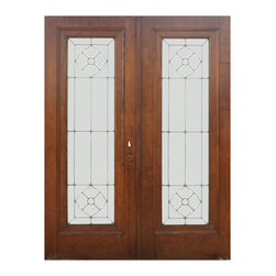 """Antique Doors - A fabulous pair of antique leaded and beveled glass doors, salvaged from a home in St. Louis and dating from the early 1900's. Each door features a long window, framed by a raised trim; at the top and bottom of each window sits a stylized flower composed of beveled glass, surrounded by a beautiful understated geometric design. The doors are in very good antique condition and are stained a beautiful brown; they measure 60"""" wide overall, 79-1/2"""" tall and 1-3/4"""" thick."""
