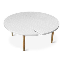 "Gus* - Root Coffee Table - Root Coffee Table  by Gus Modern    At A Glance:   Gus brings together contemporary and traditional materials in the blatantly faux Root Table. The white lacquered top has a wood pattern etched into its surface, and with the addition of the tapered ash legs, the table makes a weightless, airy impression.  What's To Like:  The Root Coffee Table gives new meaning to the term ""wood grain"" - its etched tabletop is a delightful parody of the pattern of a fresh-cut wood plank.We're especially digging the ""crack"" in the side of the table, that looks almost as if it's lightning-struck.  What's Not to Like:   If you want a wood-look coffee table, the Root Coffee Table won't be your cup of tea.  The Bottom Line:   The Root Coffee Table by Gus Modern is a whimsical, light, modern re-interpretation of a natural wood coffee table. Also see the Root End Table.  Features:    Overall: 14"" h x 36"" diam"