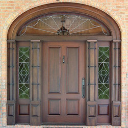 "Estate Doors - This massive entrance, DbyD-1110,  was custom built of Mahogany.  The door is 42"" X 84"" and the sidelites are 16"".  The jamb has spread mulls featuring a half double column design with pilasters,  The elliptical transom is surrounded by a wide casing with a backband.  The inside is dressed out to match the outside.  The glass is insulated Leaded Clear Glass and the hardware is Baldwin Kensington with an Oil Rubbed Bronze finish.  The door was photographed during construction.  It is installed on a custom home in Opelika, Alabama."