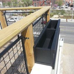 exteriorsolutionskc.com - Parapet Wall Roof Project - During a parapet wall planter application we took this picture, Over 40' of planters were installed with 6' and 8' lengths adhered without fasteners.
