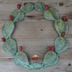 Green Patina Copper Cactus Wreath - 30 inch Green Patina Copper Cactus Wreath.  A great addition to your southwestern theme décor or to enhance a ranch entrance (gate, etc.).  Cactus pods and tunas are handcrafted from sheets of copper and welded to create a three dimensional effect that simulates a live cactus plant.  All of the pods and tunas are artfully arranged and welded to create this unique work of art.  The green patina finish and dark red tunas enhance the look – giving the wreath the appearance of a live cactus plant.  Also available in natural copper.  All wreaths are custom order.  Prices may vary depending on customer specifications.