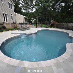 Blue Stone Pool Patio Brentwood NY  11717 – Long island - In this photo we see a pool patio made of Blue Stone in Brentwood NY (11717); the greys in these stones really make the blue of this in ground swimming pool pop. This pool is a great place for the kids to hang out over their summer break or to relax by the poolside for the adults. We also see a swing set which is another great item to have for entertaining the kids in the nice weather. Throughout out the back yard we see a variety of different types of outdoor furniture. There are lounge chairs by the pool perfect for catching some rays and in a perfect spot to hop in the pool if you get too hot. Also we see a table and chairs that are great for having guests over for a BBQ.