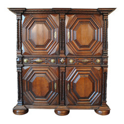 A Late 17th / Early 18th Century Italian Carved Oak Armadio - the case having four doors and three drawers with brass escutcheons and pulls, with original locks, the sections separated by double sets of turned columns, the carved door panels of octagonal form and having 4 concentric sections, resting on flattened bun feet