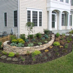 Retaining Walls - A stacked stone border wall such as this one gives you a chance to plant flowers and a garden around your home, surely giving your yard a ton of color! Visit us if you need more color in your yard. | Northern VA | Drainage & Erosion Solutions Inc