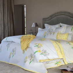 Yves DeLorme Fall Bedding - Solstice (sun) is a wonderful floral pattern of yellow irises dancing on an all white background. The duvet cover and shams reverse to an all over yellow print that simulates the pollen releasing from the flowers.  The flat sheet has a bourdon topstitch  in yellow as do the shams.  The boudoirs also have the bourdon stitich finish, but are in the abstract mimosa print (which is also the fitted sheet). The accompanying Solstice coverlet is quilted in small squares and reverses to the yellow pattern -- which also borders the front of the quilt. 100% egyptian cotton.