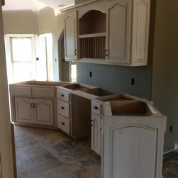 Pickled and Glazed Angled Kitchen with Plate Racks - This is a painted white kitchen we did with beaded board doors that featured two small cabinets on each side of the cooktop that were the base for a beautiful stone covered arch. The island is stained a dark stain and has bookcase ends on each end.