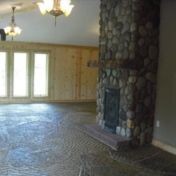 Natural Round cobblestone fireplace - A Natural Stone Fireplace made with Blue River Thin Veneer.  Installation by Landscope Masonry, stone by Sturgis Materials.