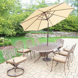 Oakland Living - 11-Pc Oval Dining Set - Includes one dining table, two swivel rockers with cushions, six stackable chairs with cushions, 9 in. tilt crank umbrella with stand and metal hardware. Fade, chip and crack resistant. Traditional lattice pattern and scroll work. Handcasted. Umbrella hole table top. Hardened powder coat. Warranty: One year limited. Made from rust free cast aluminum. Antique bronze finish. Minimal assembly required. Chair: 23 in. W x 22 in. D x 35.5 in. H (25 lbs.). Rocker: 23 in. W x 17.5 in. D x 38 in. H (33 lbs.). Table: 84 in. L x 42 in. W x 29 in. H (99 lbs.). Overall weight: 359 lbs.This dining set is the prefect piece for any outdoor dinner setting. Just the right size for any backyard or patio. We recommend that the products be covered to protect them when not in use. To preserve the beauty and finish of the metal products, we recommend applying an epoxy clear coat once a year. However, because of the nature of iron it will eventually rust when exposed to the elements. The Oakland Mississippi Collection combines southern style and modern designs giving you a rich addition to any outdoor setting.