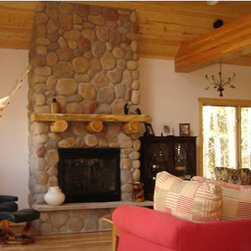 Columbine Log Home - The great room features a river rock fireplace. The live-edge timber slab mantle sits on hand peeled pine logs. A stone slab hearth creates additional seating.