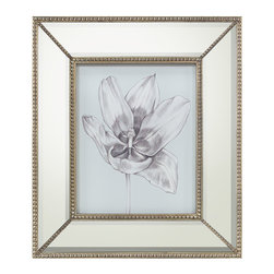 Silvery Blue Tulips II Print with Mirrored Frame - Influenced by the luxurious botanical prints gracing the garden rooms of English country manses, the artwork presents a quiet blue background that introduces an intricate illustration of a magnificent bloom balanced upon a stem, both rendered in whispers of gray. The wide mirrored frame accented with petite beading in the bevel and each corner lends a touch of refined glamour to the Silvery Blue Tulips II artwork.
