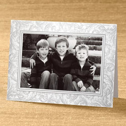 """Exposures - Luminous Flourishes Photo Christmas Card set of 18 - Overview A subtlety textured, pearlized card stock is adorned with flourishing scroll details in light silver. Embossed borders add a finishing touch. Our exclusive photo cards are the perfect way to stay in touch and share a smile with family and friends during the holiday season. Features:  Pre-printed interior verse: """"Wishing you a holiday season filled with peace and happiness"""" Specialty pearlized card stock with a linen-textured finish Embossed border detail Set of 18 photo mount cards Designed to accommodate either horizontal or vertical photos Includes adhesive dots to attach your photo Includes 20 coordinating silver foil-lined white envelopes Includes free silver foil envelope seals to add a special finishing touch   Personalization  Card personalization available in a coordinating color and font, imprinted below the pre-printed verse; up to 3 lines, 50 characters per line  Select horizontal or vertical placement to match orientation of your photo Envelope personalization available in a coordinating color and font, imprinted on the back flap of the envelope; up to 3 lines, 48 characters per line   Specifications  Folded card size 8"""" wide x 6"""" high Holds one horizontal or vertical 4"""" x 6"""" photo   Shipping  Please allow an additional 2 weeks for imprinted items No returns on personalized items unless the item is damaged or defective"""