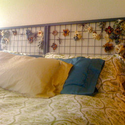 Repurposed Headboard - I painted the old mattress frame from an Ikea loft bed, and applied flowers which I made from old fabric samples, vintage buttons, and yarn.  I then installed the frame to the wall using the existing holes.  I chose rust-colored deck screws for extra detail.  See the project here: http://mygroovyentropy.blogspot.com/2011/08/repurposing-with-flower-power_22.html