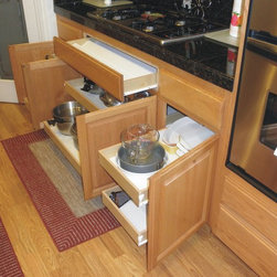 Roll Out Shelves/Pull Out Shelves in Kitchen - Custom roll out shelves (pull out shelves) installed under a cook top.  We also added a drawer under the cook top using the false front.  Our clients love this feature to store their cooking utensils in a convenient place.