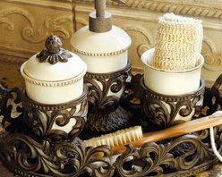 The GG Collection Vanity Set (3 Piece) - New from the GG Collections this set of creamy ceramic vanity accessories are cradled in elaborate hand-crafted bases. The set includes soap dispenser, cup and covered container. It is displayed here in the Oval Tray (sold separately). Beautiful, Italian-inspired, ceramic serving pieces with burnished metal accents by the GG Collection. This exceptional line of goods, for gracious entertaining, brings Old World elegance and style to your home.